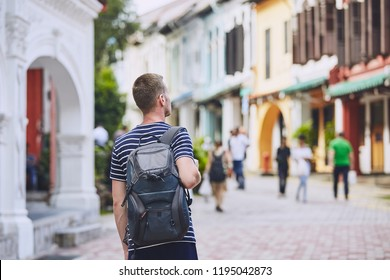 Traveler in city. Young man with backpack admiring architecture of old houses in Singapore.