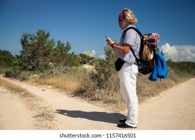 Traveler consults his mobile phone at a crossroads in a rural landscape