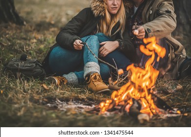 Traveler couple camping and roasting marshmallows over the fire in the forest after a hard day. Concept of trekking, adventure and seasonal vacation.