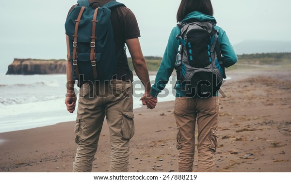 Traveler couple in love with backpacks walking on sea beach in summer and holding each other hand