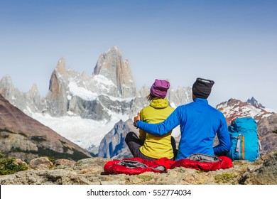 Traveler couple in love enjoying the view of majestic Mount Fitz Roy - symbol of Patagonia, Argentina