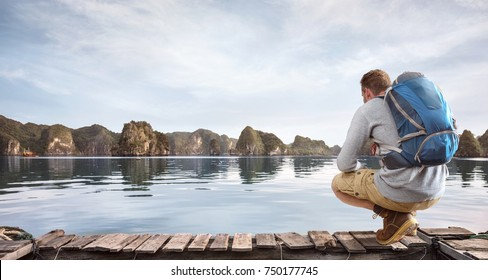 Traveler crouching on a jetty