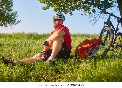 Traveler cyclist have a rest under oak tree with his bike behind him on summer afternoon.