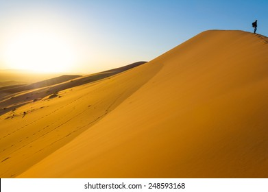 Traveler in the desert, active young woman trekking in hot sandy wilderness, dramatic sunset, summertime adventure, extreme tourism concept
