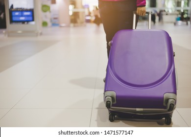 Traveler dragging luggage or baggage at airport when traveler woman come back to her country or traveler girl travel to overseas or foreign country for vacation and she just arrived and walk to gate
