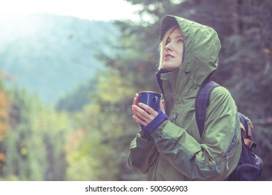 Traveler drink hot tea or coffee in forest in autumn meeting sunrise in mountains, toned image
