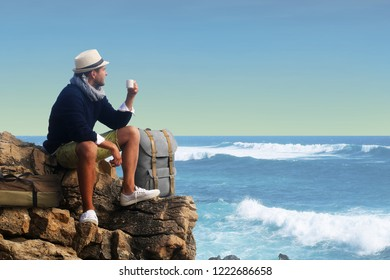 Traveler drinking coffee against the waves of the ocean