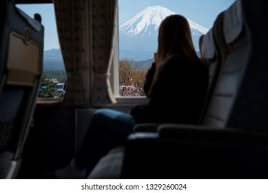 Traveler enjoy looking a view from train window with Beautiful Mount Fuji on background.