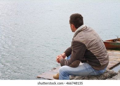 Traveler enjoying lake view. Man looking at horizon, depression, loneliness concept.