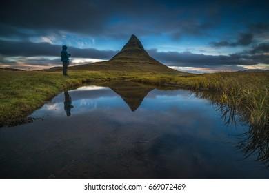 Traveler enjoying scenic landscape at Kirkjufell Mountain in Western Iceland. Shallow depth of field