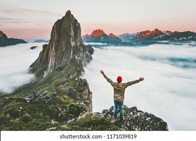 Traveler enjoying sunset Segla mountain hiking adventure outdoor in Norway active vacations traveling lifestyle man raised hands on cliff above clouds