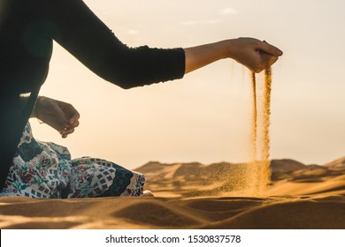 Traveler explorer girl sitting in the Sahara Desert and letting the sand fall from the hand, Morocco, Africa