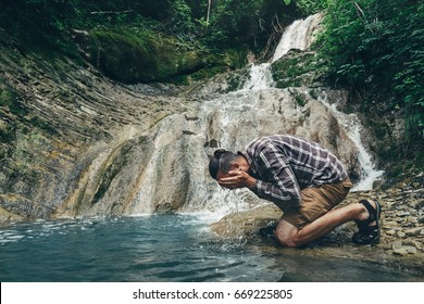 Traveler Explorer Washing His Face In Wild River Destination Experience Lifestyle Concept