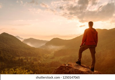 Traveler explorer young man standing on top of rock in the mountains at sunset and enjoying view of nature.