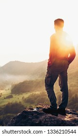 Traveler explorer young man standing on peak of cliff at sunset and enjoying view of nature in summer.