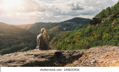 Traveler explorer young woman sitting on rocky stone and looking at mountain valley in autum, rear view.