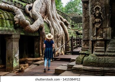 Traveler exploring the ancient ruins of Ta Prohm temple at Angkor, Siem Reap, Cambodia.