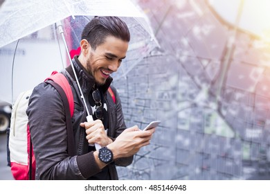 Traveler exploring the city on a rainy day with a smartphone and next to a street map