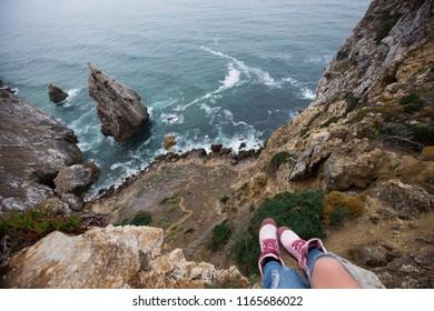 Traveler feet above ocean cliff