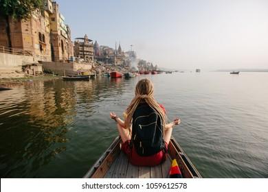 Traveler female wearing dreadlocks seating in wooden boat and enjoy Varanasi view