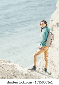 Traveler girl with backpack walking on high coast on background of sea in summer.