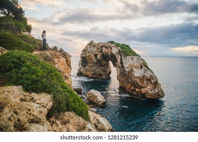 Traveler girl on a high cliff watching the beautiful views of Mallorca Island, Spain