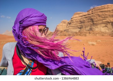 traveler girl portrait with bright pink flowing hair at speed, sit on a pickup car in travel tour in Wadi Rum Jordanian Middle East desert heritage place