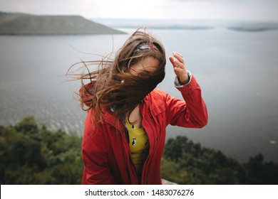 Traveler girl in red raincoat and with windy hair standing on top of rock mountain with beautiful view on river. Young hipster woman relaxing on cliff. Travel and wanderlust. Copy space