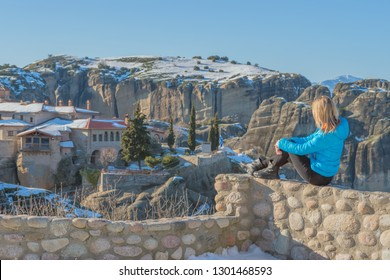 A traveler girl sits high against the rocks of the Meteora monastery in Greece on a bright sunny day.