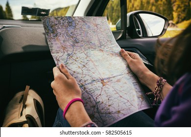 traveler girl sitting in the car looking map. Dolomites, Italy.