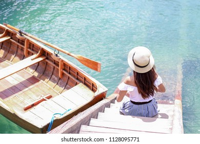 Traveler girl sitting at pier next to rowboat with clear water of Lago di Braies lake in South Tyrol,Italy.woman on vacation