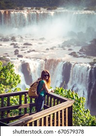 traveler girl and view of worldwide known Iguassu falls at the border of Brazil and Argentina