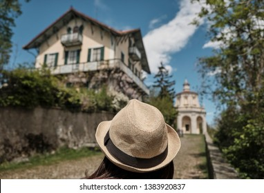 Traveler girl with Vintage Straw hat looking monumets and one of the XIVchapel along the path of the historic pilgrimage route from Sacred Mount or Sacro Monte of Varese, Italy - Lombardy
