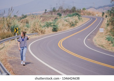 traveler girl walking on the road in mountain outdoor by wearing lanna shirt north and jeans Thailand