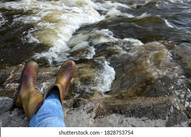 A traveler at a halt on the bank of a river. A traveler in rubber boots made a halt by the river. Camping by the river. Pause in business. Rethinking and Meditation. - Shutterstock ID 1828753754