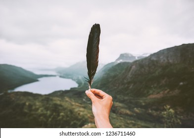 Traveler hand holding feather in mountains Traveling alone adventure lifestyle melancholy solitude emotions moody landscape nature