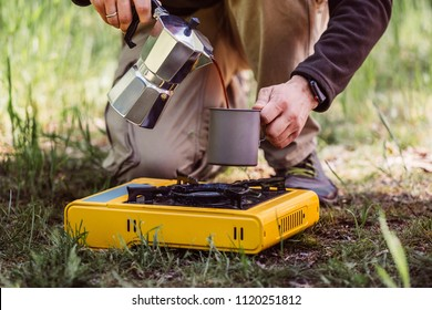 Traveler hands holding coffeepot and pouring coffee in cup near camping stove. Tourist man cooking with coffee maker and drinking from mug on picnic. Hiker with travel pot outdoors on nature.