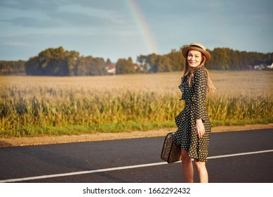 traveler happy girl. woman with a suitcase rejoices rainbow after rain