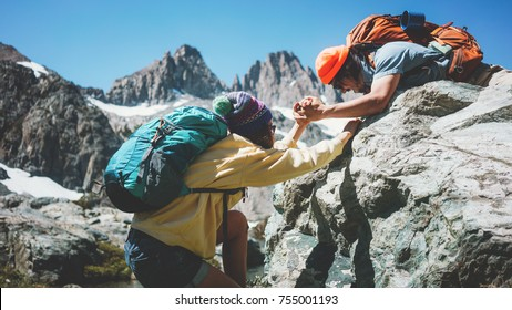 Traveler helping his friend to climb a rock. Young active couple with backpacks in stunning snowy mountain wilderness near the lake
