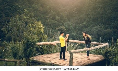 traveler hike and camping in summer concept from asian couple take photo and see view with tropical forest background