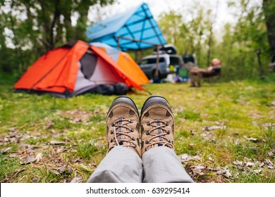 Traveler hiking boots near camping tent outdoors. Trekking shoes on nature campsite in the forest. Travel healthy active lifestyle freedom background. Feet selfie. Woman relaxing after hiking.