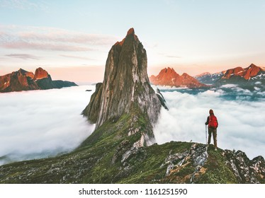 Traveler hiking on mountains ridge over clouds adventure journey traveling outdoor in Norway active vacations sunset Segla mountain