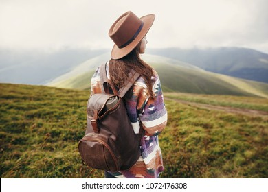 traveler hipster girl in hat with backpack exploring misty sunny mountains in clouds. space for text. stylish woman traveling. amazing atmospheric moment. travel and wanderlust concept.