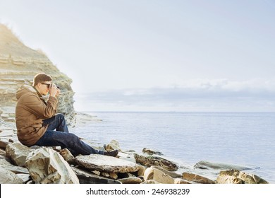 Traveler hipster young man sitting on coastline near the sea and taking photographs with vintage photo camera