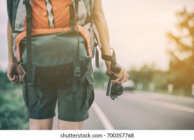 traveler hold mirrorless camera in his hands with blur background and sunlight in summer time, selective focus. Photo of Vintage and filtered process.