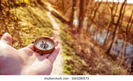 Traveler holds a compass in his hand, traveling around the world, looking for a road, close-up