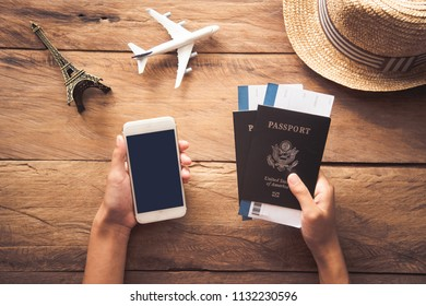 Traveler holds passport and smart phone. Along with travel