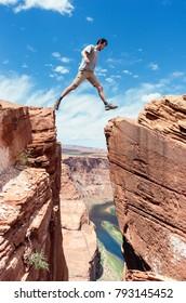 traveler jumps over rock at Horseshoe Bend in Utah, USA