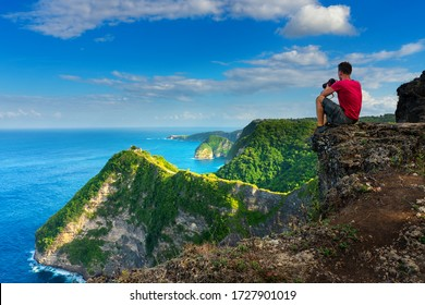 Traveler look at the ocean and rocks. Travel and active life concept. Adventure and travel on Bali, Indonesia.