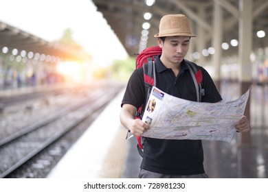 traveler look searching direction on location map while traveling and sit on the bench at train station and searching road to hotel on map foreign city during vacation at Hua Lamphong Bangkok Thailand
